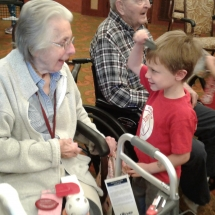 Kinder-care-Shoreview Senior Living-child showing a tenant his comb