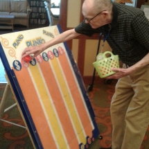 Labor Day Fair Games-Shoreview Senior Living-dropping in a chip for plinko