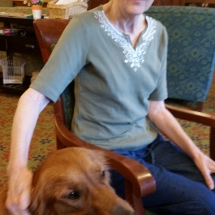 Tea and Trivia with Leo-Shoreview Senior Living-Leo getting cozy with a tenant